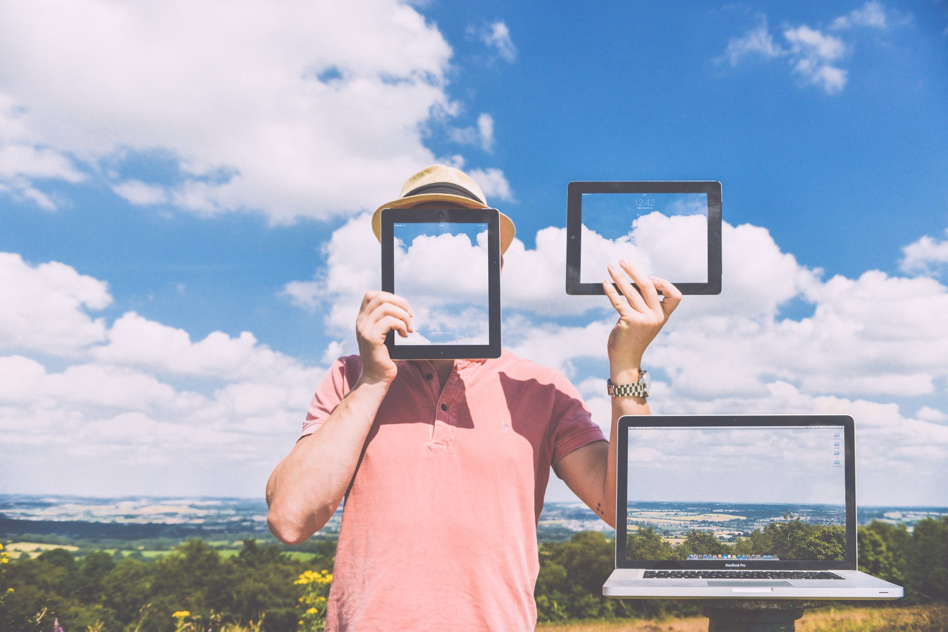 photo of a man holding a tablet in front of his face, one in his raised left hand, in front of a sky background. A laptop is in the right corner.