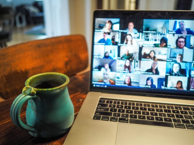 image of a cup next to a macbook displaying a videoconference